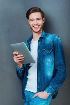 Mijn digitale vriend. gelukkige jonge man die digitale tablet vasthoudt en naar de camera glimlacht