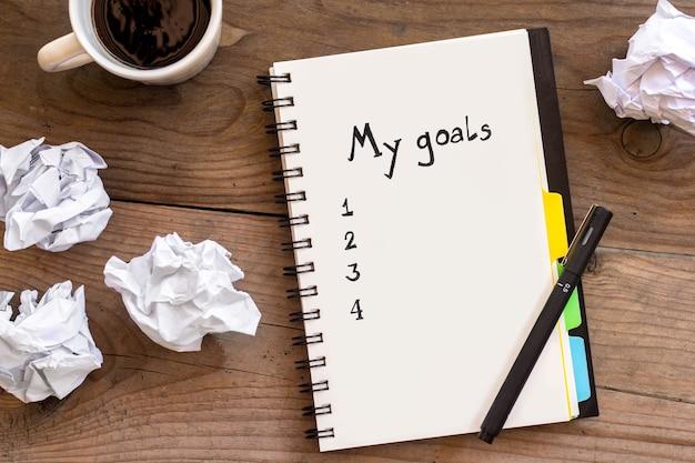 Mijn doelenlijst op een notitieboekje met verfrommeld papier en een kopje koffie op houten achtergrond