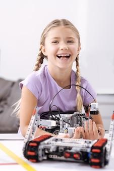 Mijn eerste technische project. vrolijk gelukkig positief meisje dat zich op school bevindt en elektronische robot vasthoudt terwijl zij geluk uitdrukt