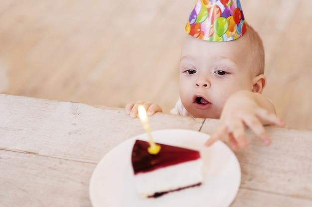Mijn eerste verjaardagstaart! bovenaanzicht van schattige kleine baby in feestmuts die de hand uitstrekt naar het bord met cake en de mond openhoudt