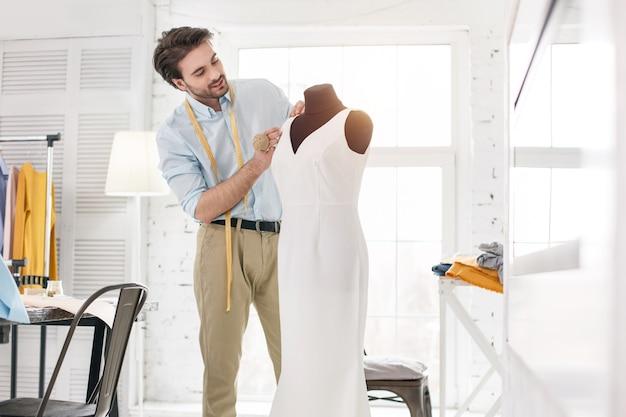 Mijn favoriete bezigheid. uitbundige jonge kleermaker die in zijn kantoor werkt en een nieuwe jurk maakt