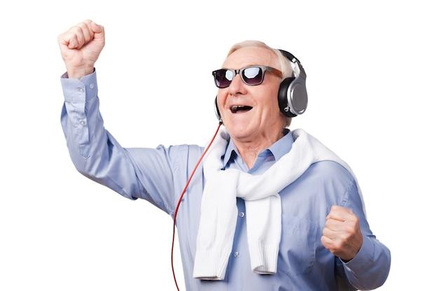 Mijn favoriete lied! vrolijke senior man met koptelefoon die zijn armen omhoog houdt en positiviteit uitdrukt terwijl hij tegen een witte achtergrond staat