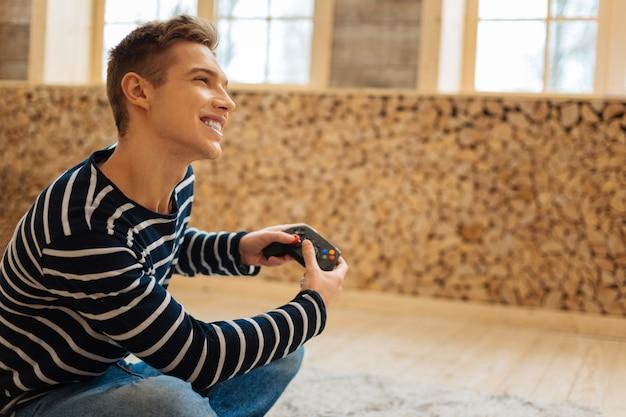 Mijn favoriete spel. goed uitziende uitbundige blonde jonge man glimlachend en met een afstandsbediening voor games zittend op de vloer