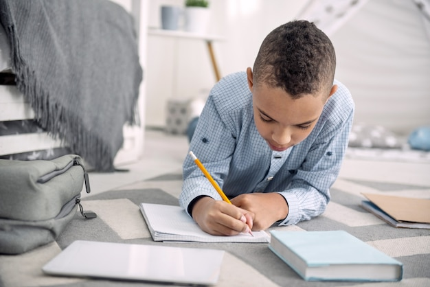 Mijn gedachten. geconcentreerde afro-amerikaanse jongen liggend op de vloer tijdens het schrijven in notitieblok
