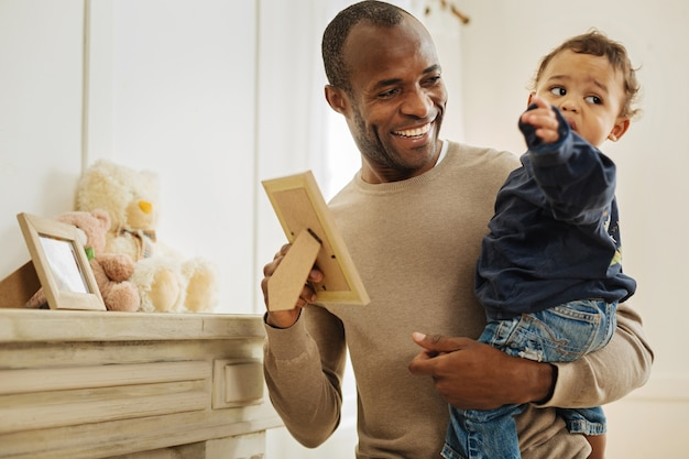 Mijn geliefde zoon. uitbundige donkerharige afro-amerikaanse man die lacht en foto's laat zien aan zijn zoon terwijl hij hem in zijn armen houdt