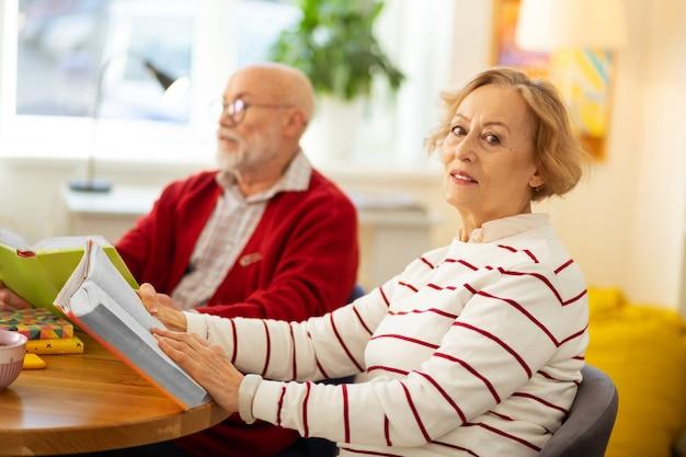 Mijn hobby. aardige knappe vrouw die naar je kijkt terwijl ze met een boek aan tafel zit