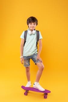 Mijn hobby. alert knappe jongen draagt een schooltas en staat op zijn skateboard