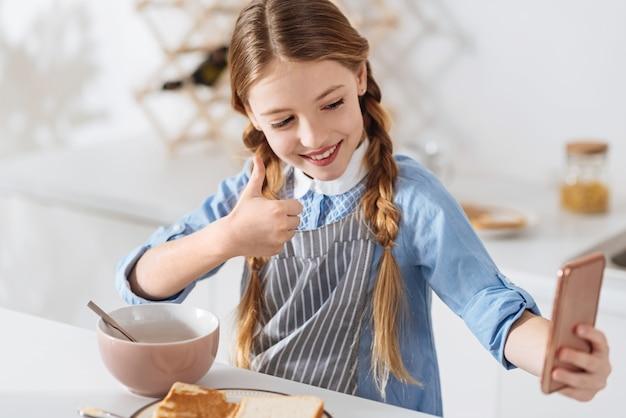 Mijn humeur delen. charismatisch goed uitziend lief meisje dat haar gadget gebruikt om een selfie te maken voor haar vrienden terwijl ze een ontbijt heeft bestaande uit ontbijtgranen en sandwiches