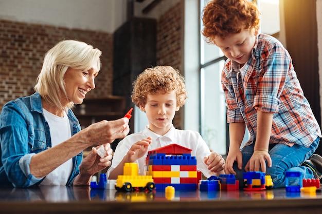 Mijn kleinkinderen zijn mijn schatten. selectieve aandacht voor een geconcentreerde jongen, gekleed in een wit overhemd en een gelukkige senior vrouw grijnzend