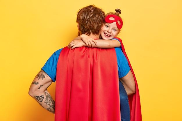 Mijn lieve super vader. aanhankelijk klein kind knuffelt vader met liefde, draagt rood masker