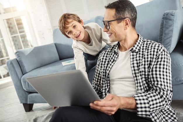 Mijn lieve zoon. leuke waakzame blonde jongen die lacht en achter zijn vader zit en zijn vader die op de laptop werkt