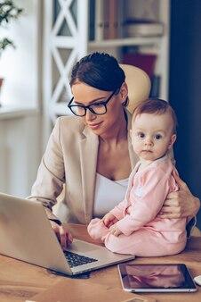 Mijn mama is een echte expert! klein babymeisje dat naar de camera kijkt terwijl ze op een bureau zit met haar moeder op kantoor