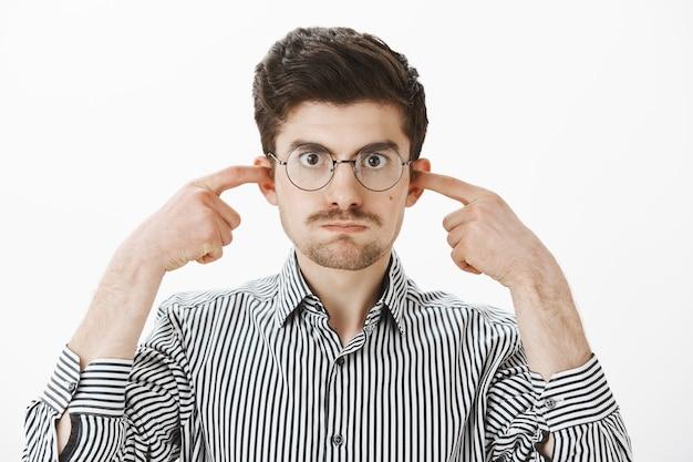 Mijn minuten kloppen van je gesprekken. geërgerd beu blanke man in bril, adem inhoudend en oren sluiten met wijsvingers, gekweld en ontevreden kijkend met vervelende geluiden over grijze muur
