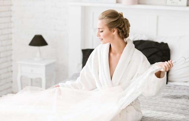Mijn mooie jurk. charmante vrolijke jonge bruid zittend op het witte bed thuis en tederheid uiten terwijl je je klaarmaakt voor de huwelijksceremonie en de trouwjurk vasthoudt