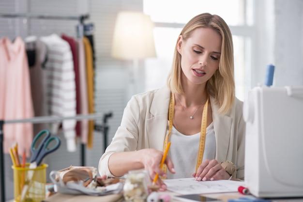 Mijn startup. meditatieve vrouwelijke couturier tekening schets terwijl je naar beneden kijkt