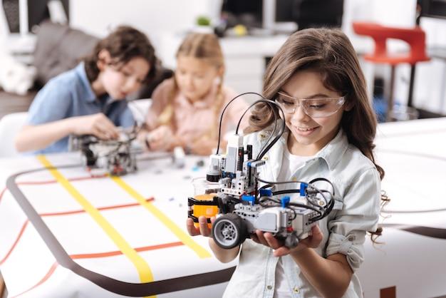 Mijn vaardigheden toepassen. blij optimistisch jong meisje dat op school staat en elektronische robot vasthoudt terwijl collega's aan het project werken