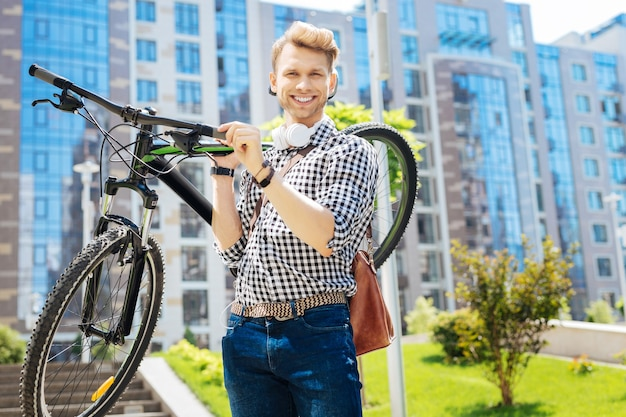 Mijn voertuig. positieve sterke man die lacht terwijl hij zijn fiets vasthoudt