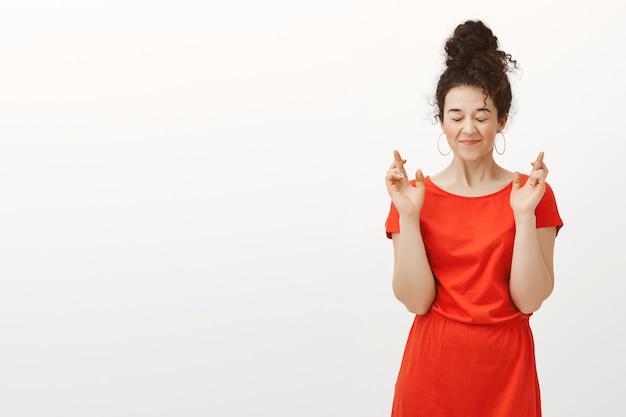 Mijn wens komt zeker uit. grijnzende gelukkige europese vrouw in rode jurk met haar in een broodje gekamd