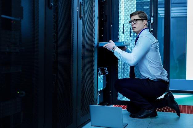 Mijn werkdag. geïnspireerde professionele operator die werkt met serverapparatuur op kantoor