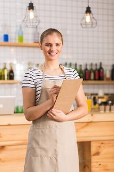 Mijn werkplek. gelukkig positieve jonge vrouw uniform dragen en notities schrijven tijdens het werken in de cafetaria