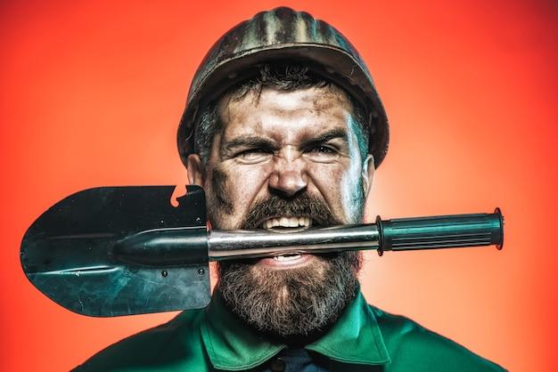 Mijnbouw- en bouwconcept man met boos gezicht in beschermende helm houdt schop in tanden