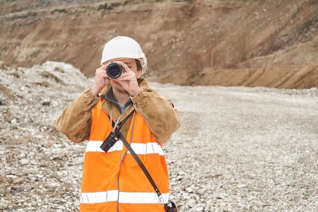 Mijnbouw- of wegenbouwkundige die een telescoop gebruikt tegen de achtergrond van een mijn