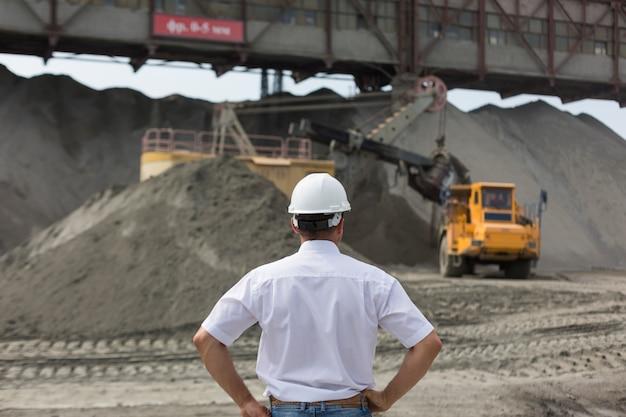 Mijnbouwingenieur in helm houdt toezicht op het werk van de granietworkshop