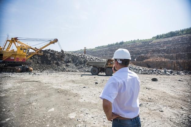 Mijnbouwingenieur in wit overhemd en helm houdt toezicht op het laden van dumpers in een steengroeve