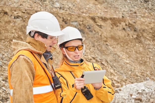 Mijningenieurs bespreken werkdocumentatie buiten op de mijnsite