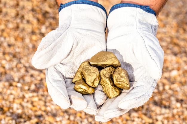 Mijnwerker hand met stenen uit een ander, goud minerale winning, edelsteen exploratie concept.