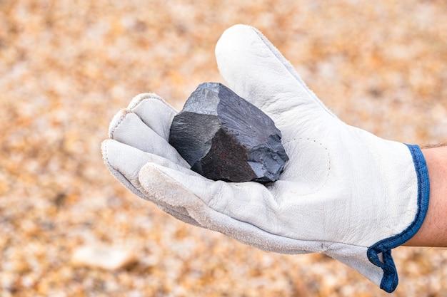 Mijnwerkershand met ijzeren steen, metallisch ijzer pyriet, staal, gebruikt in zware industriële productie