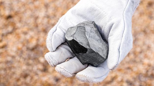 Mijnwerkershand met ijzeren steen, metallisch ijzerpyriet, staal, gebruikt in zware industriële productie. mineraal extractie concept.