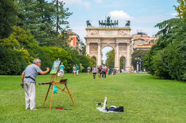 Milan, italië - 14.08.2018: kunstenaar trekt boog van vrede in sempione park.
