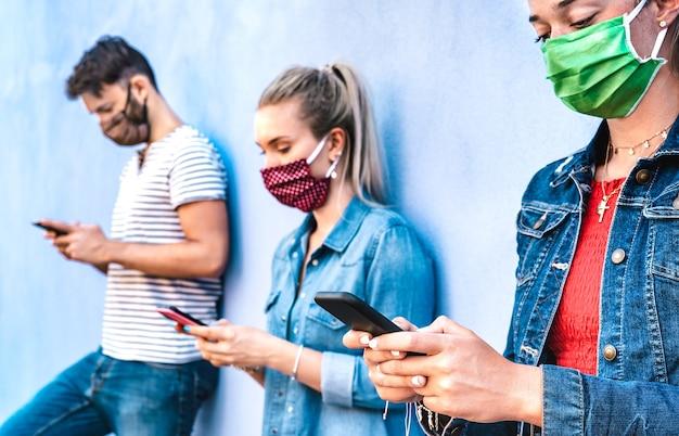 Milenial vrienden met behulp van mobiele telefoon gedekt door gezichtsmasker