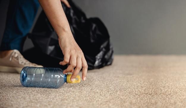 Milieu ecologie zorg hernieuwbaar concept vrijwilliger die plastic flesafval inzamelt
