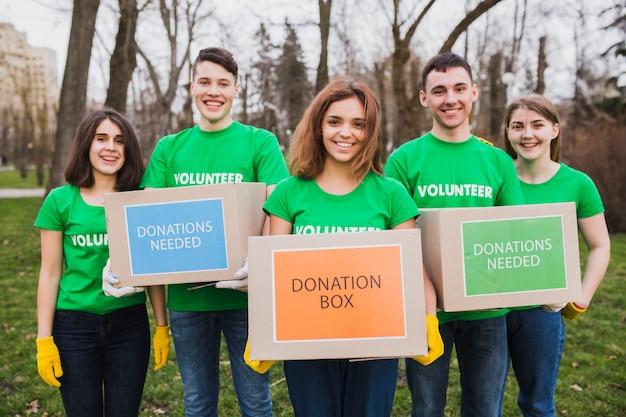 Milieu en vrijwilligersconcept met personen die dozen voor schenkingen houden