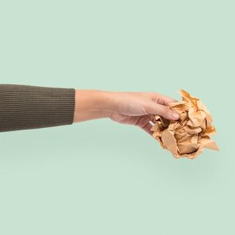 Milieu van recyclebaar papier, vastgehouden door een hand