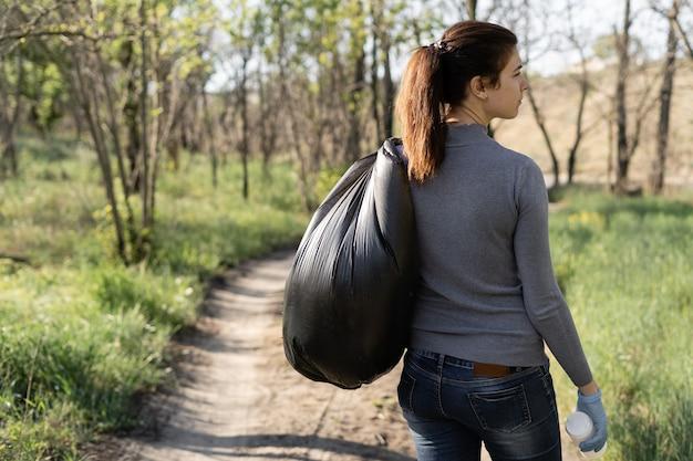 Milieubescherming concept. vrouw draagt een volle vuilniszak op haar schouder. vrijwilliger maakte het park schoon