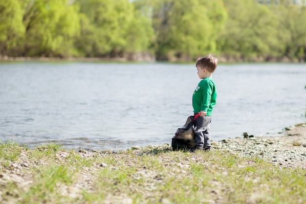 Milieuconcept opslaan, een kleine jongen die afval en plastic flessen op het strand verzamelt