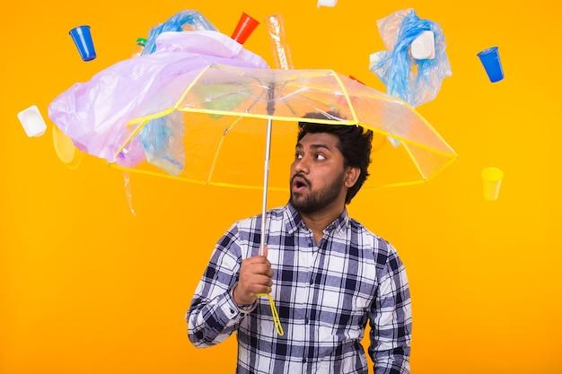 Milieuvervuiling, plastic recycling probleem en ecologie probleem concept - bang indiase man staat onder afval met paraplu