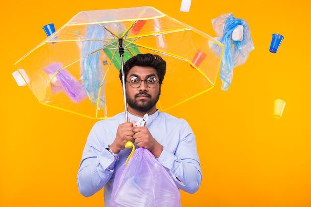 Milieuvervuiling, plastic recycling probleem en ecologie probleem concept - trieste indiase man met vuilniszak