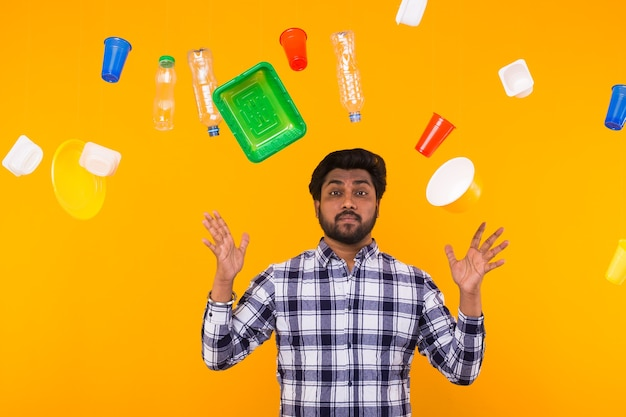 Milieuvervuiling, plastic recyclingprobleem en ecologieprobleemconcept - trieste indiase man omringd door afval