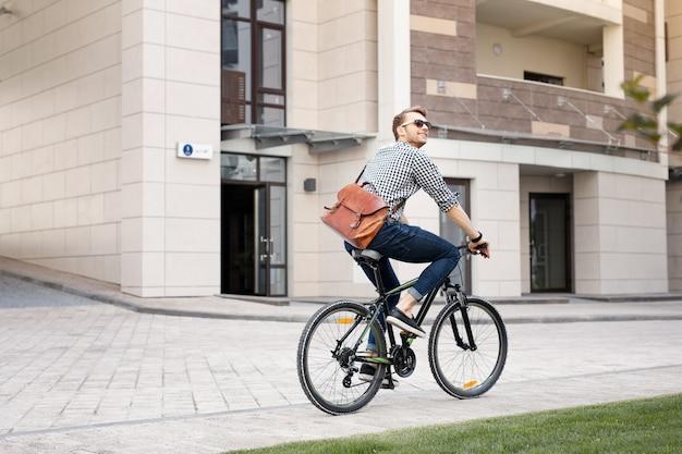 Milieuvriendelijk. gelukkig positieve man fietsen terwijl hij naar zijn werk gaat