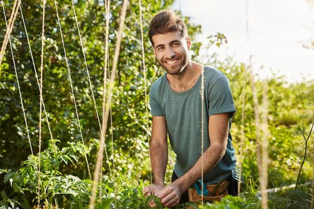 Milieuvriendelijk. gezond levensstijlconcept. buiten portret van jonge aantrekkelijke bebaarde blanke mannelijke boer lachend in de camera, bezig met zijn boerderij, groenten planten.