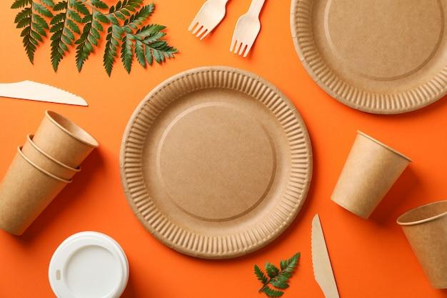 Milieuvriendelijk servies en plant op oranje, bovenaanzicht