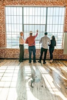 Milieuvriendelijk technisch team in gesprek bij de glazen ramen