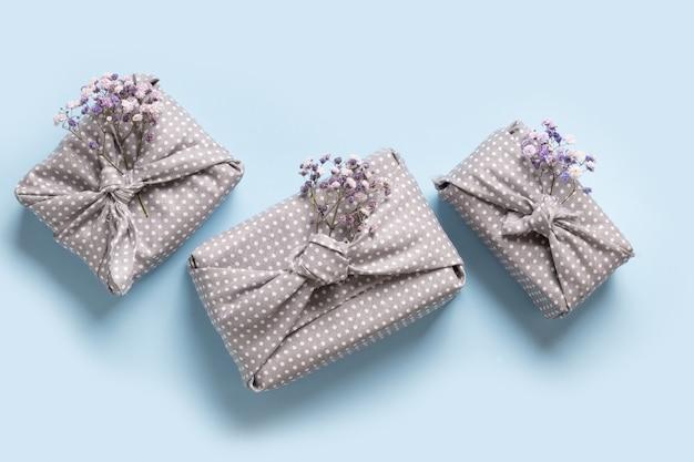 Milieuvriendelijk voorjaarscadeau verpakt in grijs textiel met bloemen op blauw.