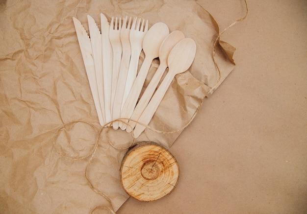 Milieuvriendelijk wegwerp keukengerei op verfrommeld kraftpapier. houten vorken, lepels en messen. recycling van servies en hergebruik.zorg voor het milieu.