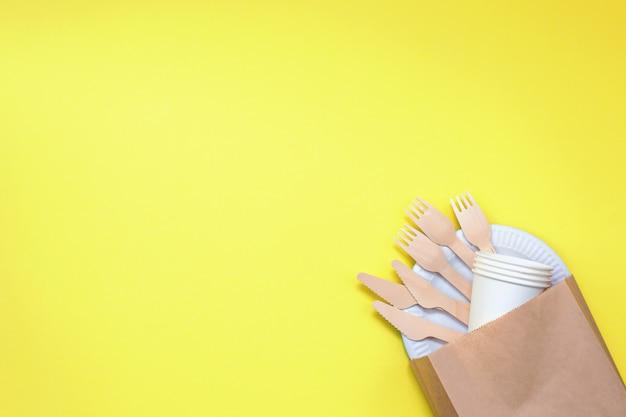 Milieuvriendelijk wegwerpgereedschap gemaakt van bamboehout en papier op gele achtergrond.