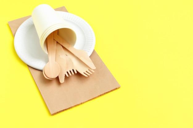 Milieuvriendelijk wegwerpgerei van bamboehout op papieren zak op geel